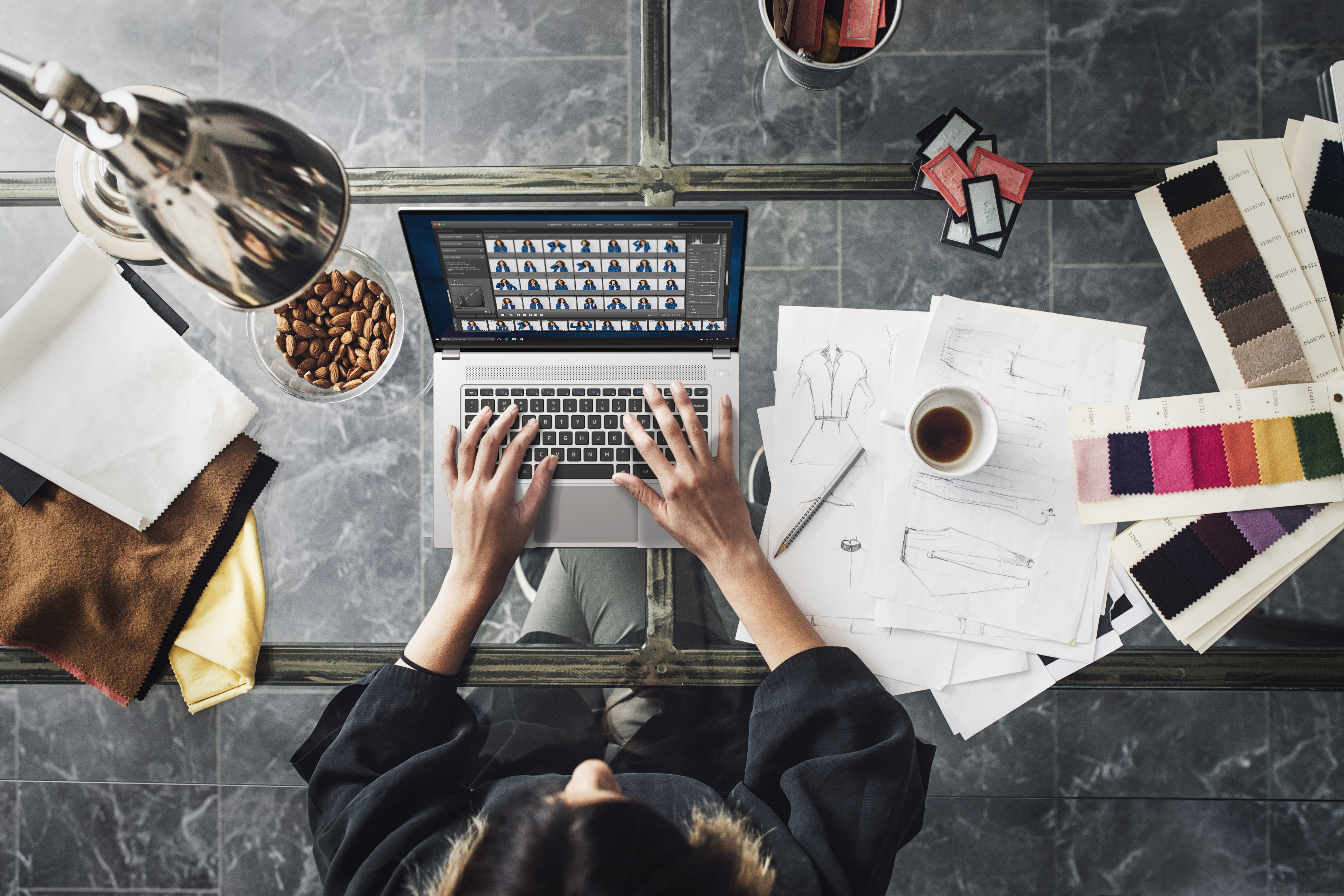 From above photo of unrecognisable woman designer typing on her laptop.